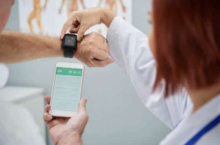 Doctor showing senior patient how to synchronize health app in smartphone and smartwatch